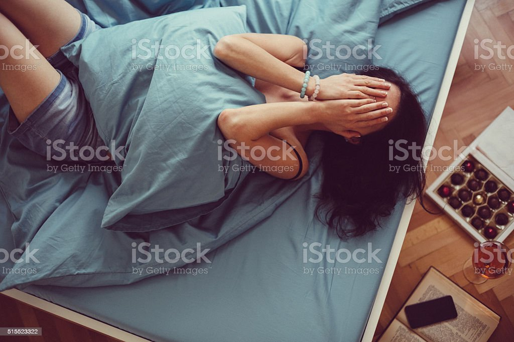 Girl crying in bed stock photo