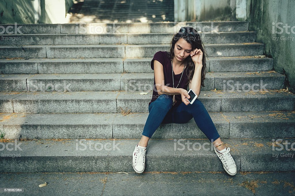 Girl crying on stairs stock photo