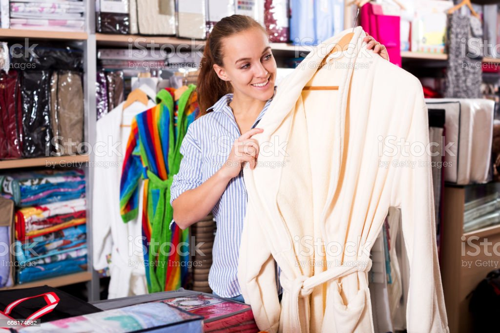 Girl customer deciding on the choice of bathrobe stock photo