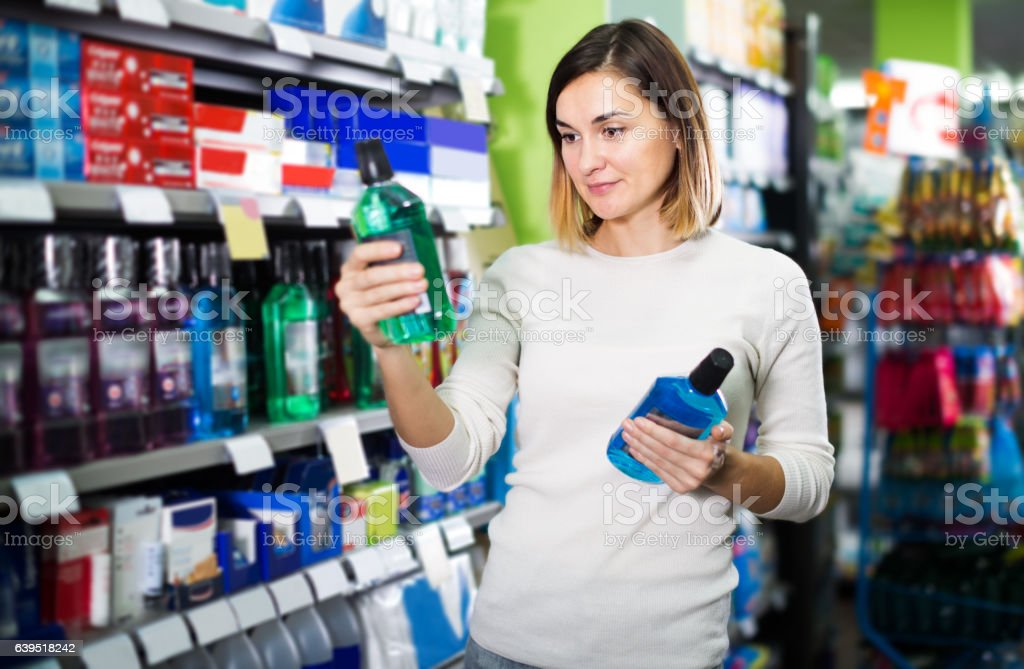 Girl customer looking for effective mouthwash in supermarket stock photo