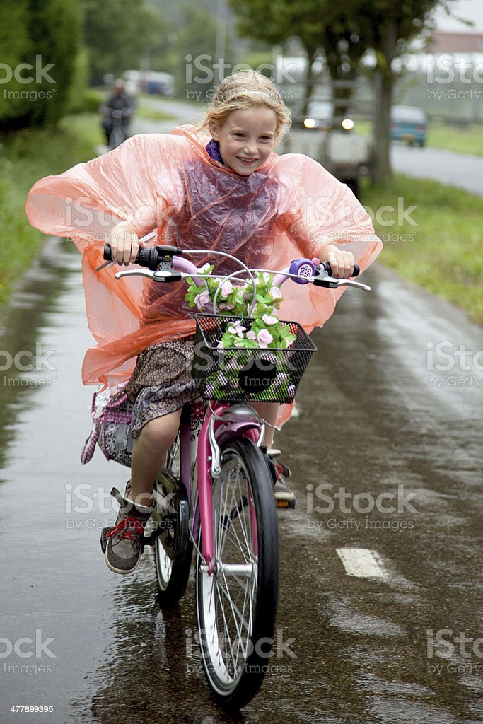 girl cycling in the rain stock photo