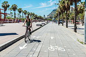 Girl cycling on the promenade in Barcelona