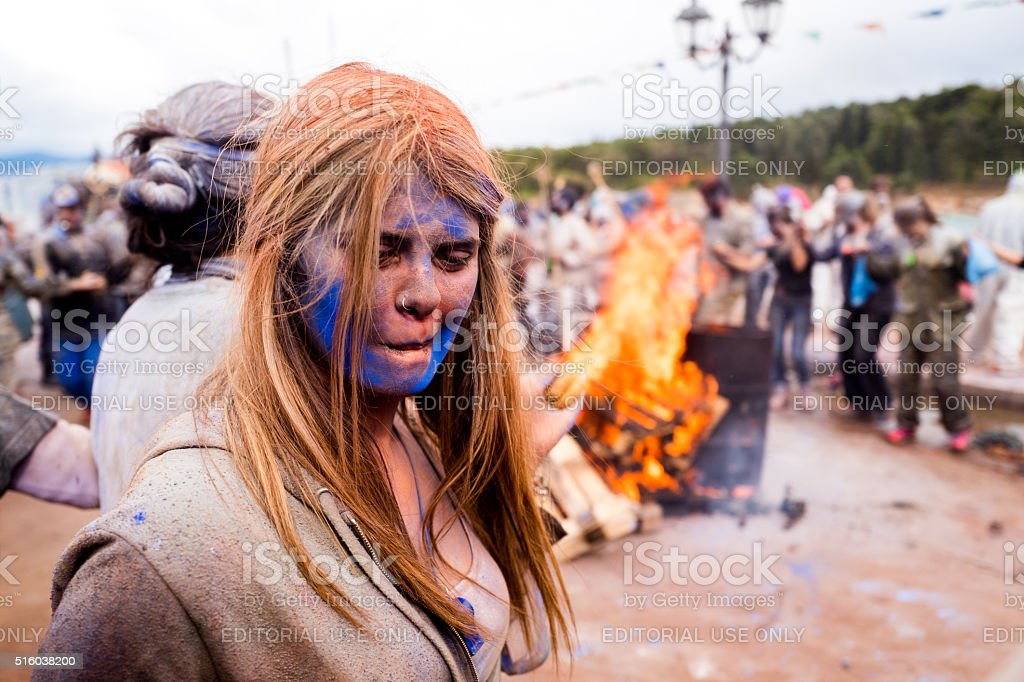 Girl dancing around a fire at flour fighting in Greece stock photo