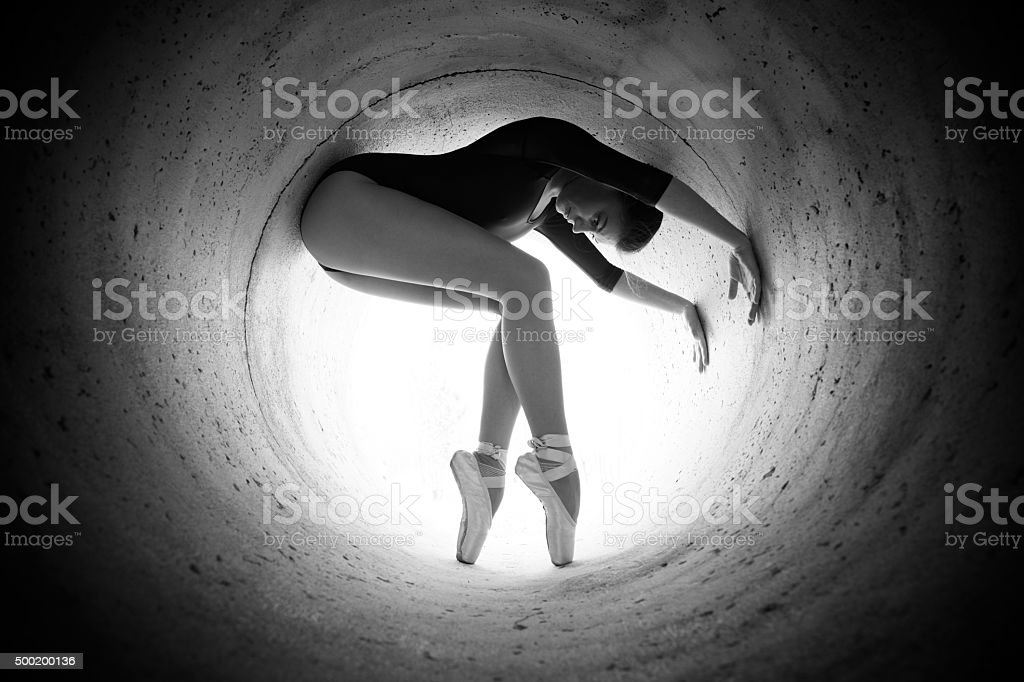 Girl dancing in the tunnel with the light end stock photo