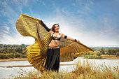 Girl dancing with golden wings.