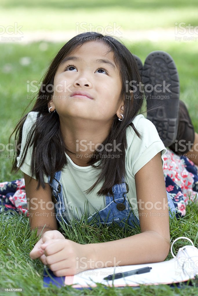 Girl daydreaming while doing homework outside royalty-free stock photo