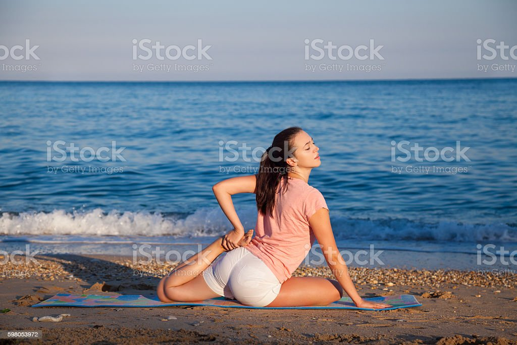 girl deals with Yoga on the beach stock photo