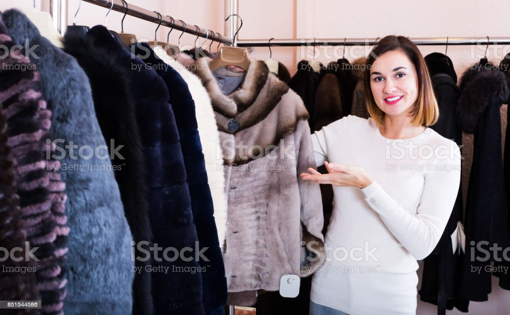 Girl deciding on fur jacket stock photo