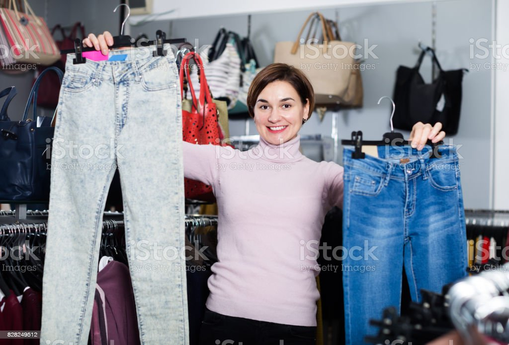 Girl deciding on new jeans stock photo