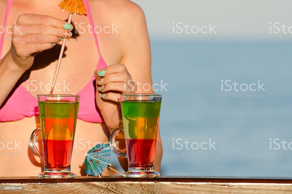 Girl decorates the cocktail on the beach stock photo