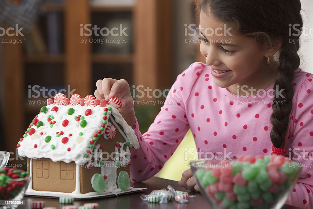Girl decorating gingerbread house stock photo