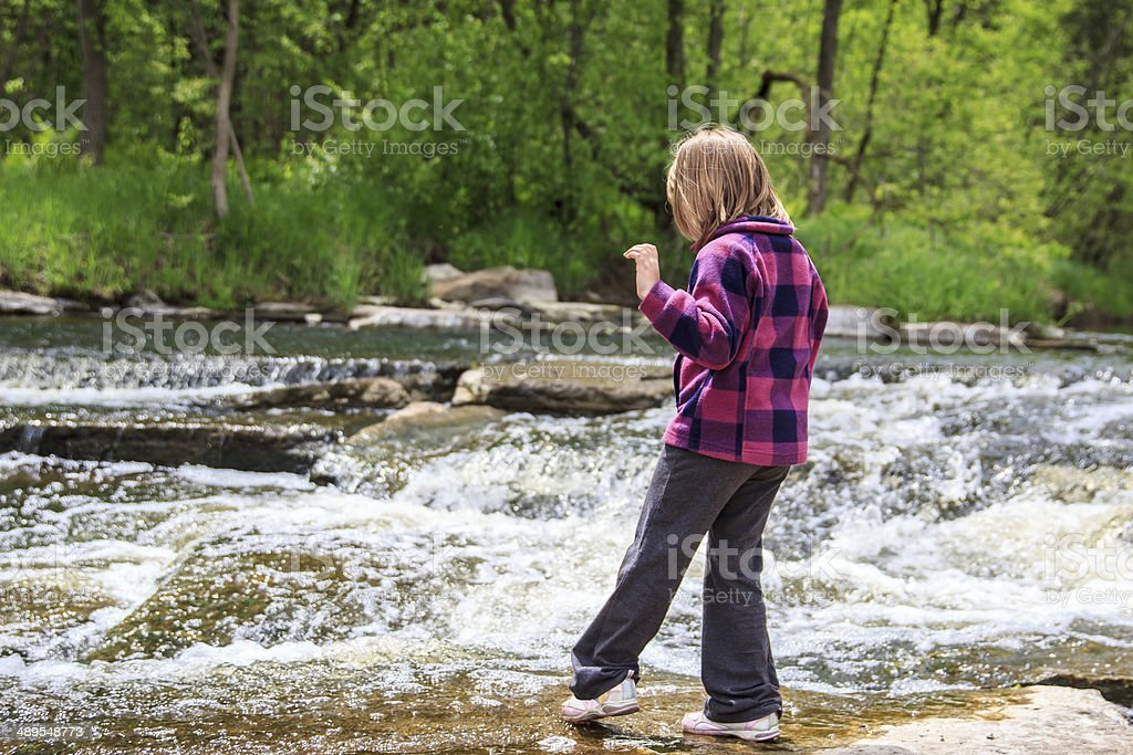 Girl Dipping Her Toe in the Water stock photo