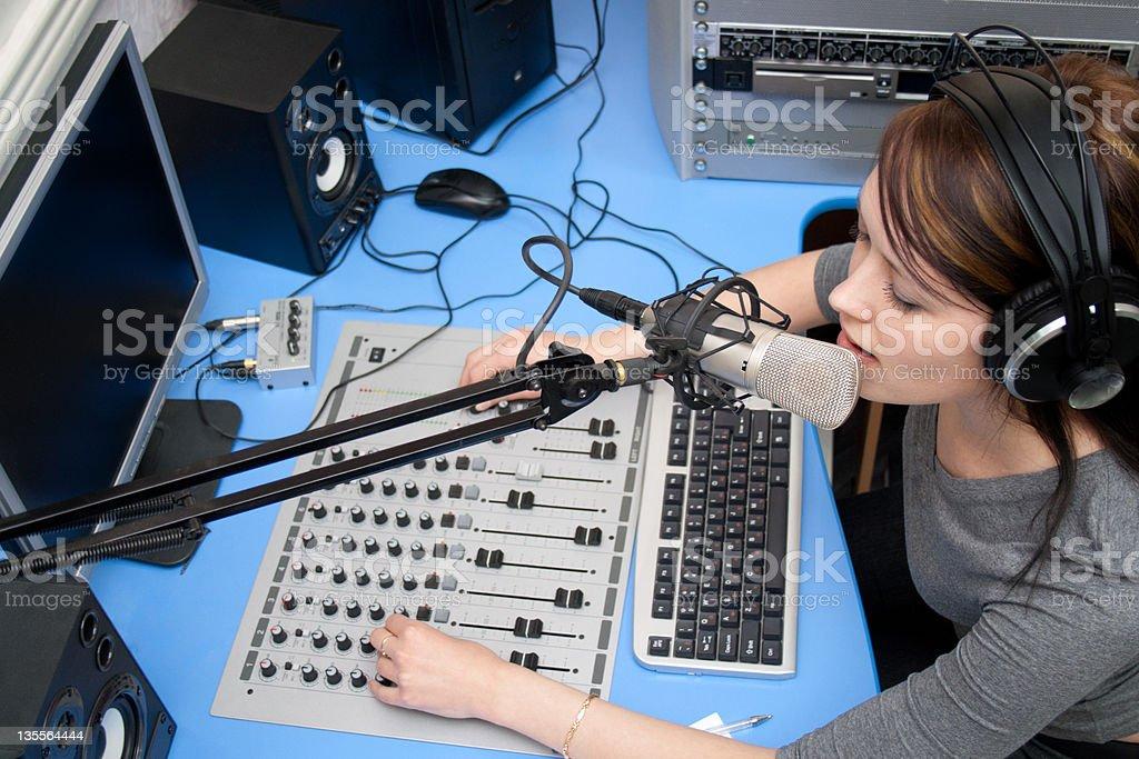 Girl DJ broadcasting live in the studio royalty-free stock photo