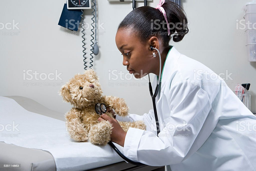 Girl doctor using stethoscope on teddy bear stock photo