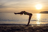 girl does exercises on the seashore at dawn