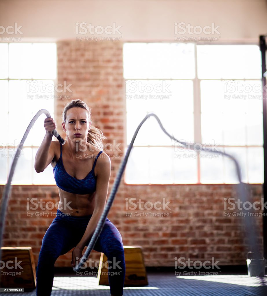 Girl doing fitness workout with ropes in gym stock photo
