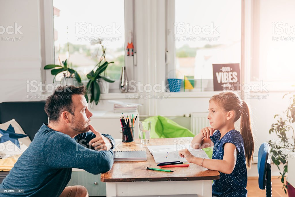 Girl doing homework and contemplating stock photo
