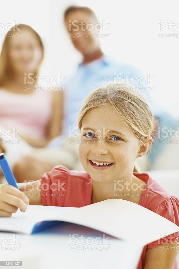 Girl doing homework with her parents in the background royalty-free stock photo