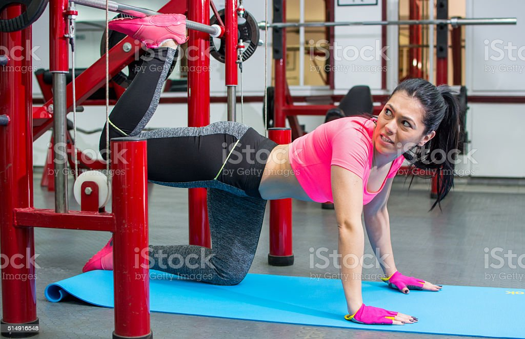 Girl doing leg and glute workout at the gym stock photo