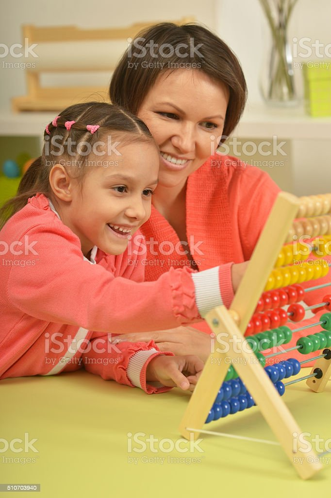girl doing math exercises with  mother stock photo