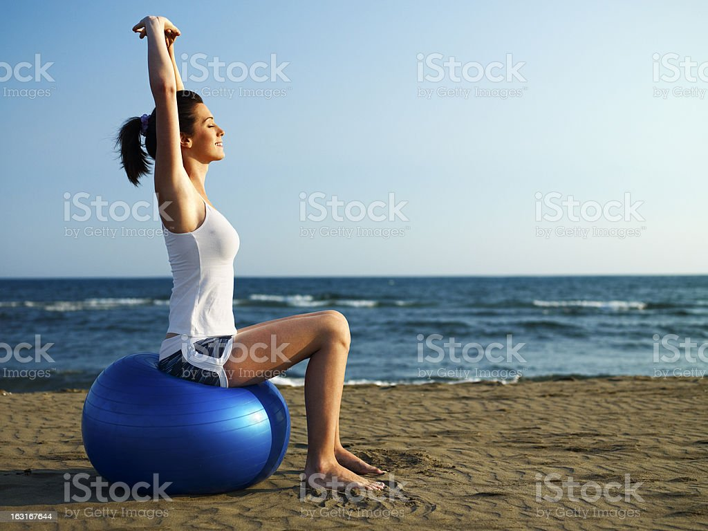 Girl doing pilates on the beach royalty-free stock photo
