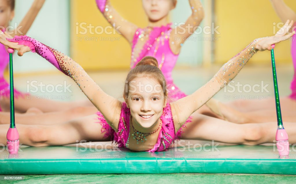 Portrait of beautiful preteen girl doing rhythmic gymnastics with...