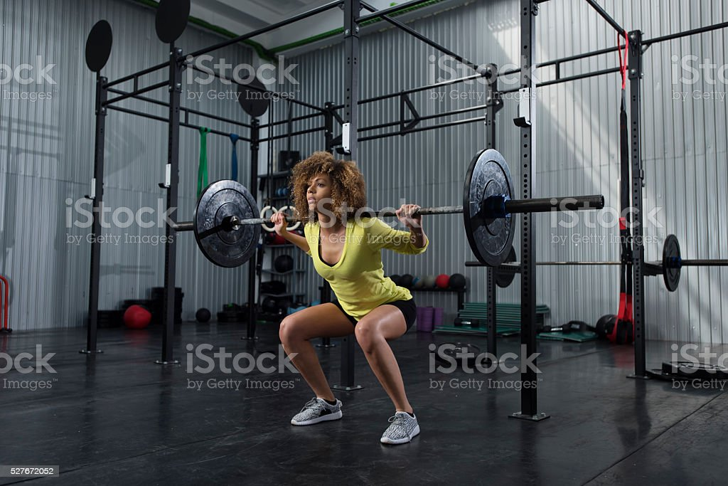 Girl doing squats at the gym stock photo