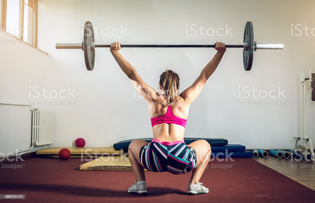 Girl doing squats with weight stock photo