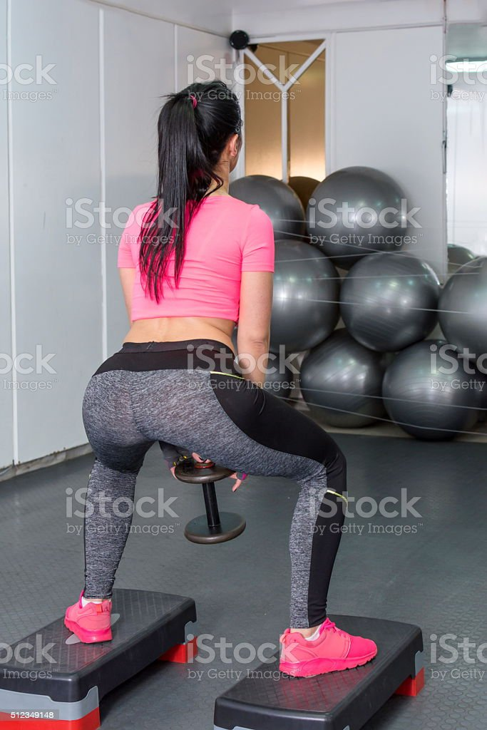 girl doing squats with weights stock photo
