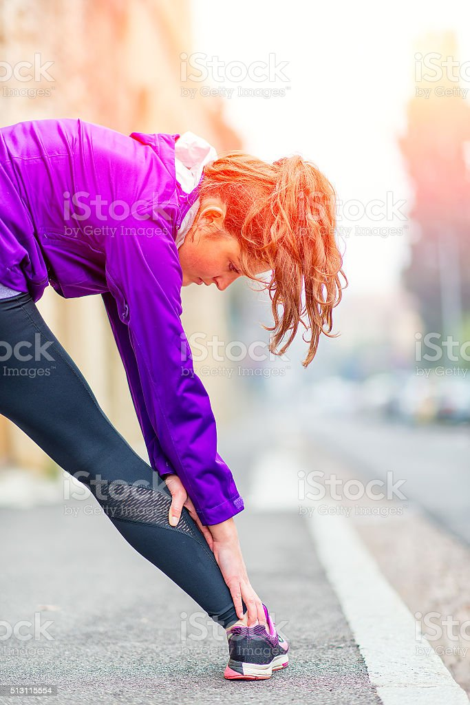 Girl doing stretching on the sidewalk in the city stock photo