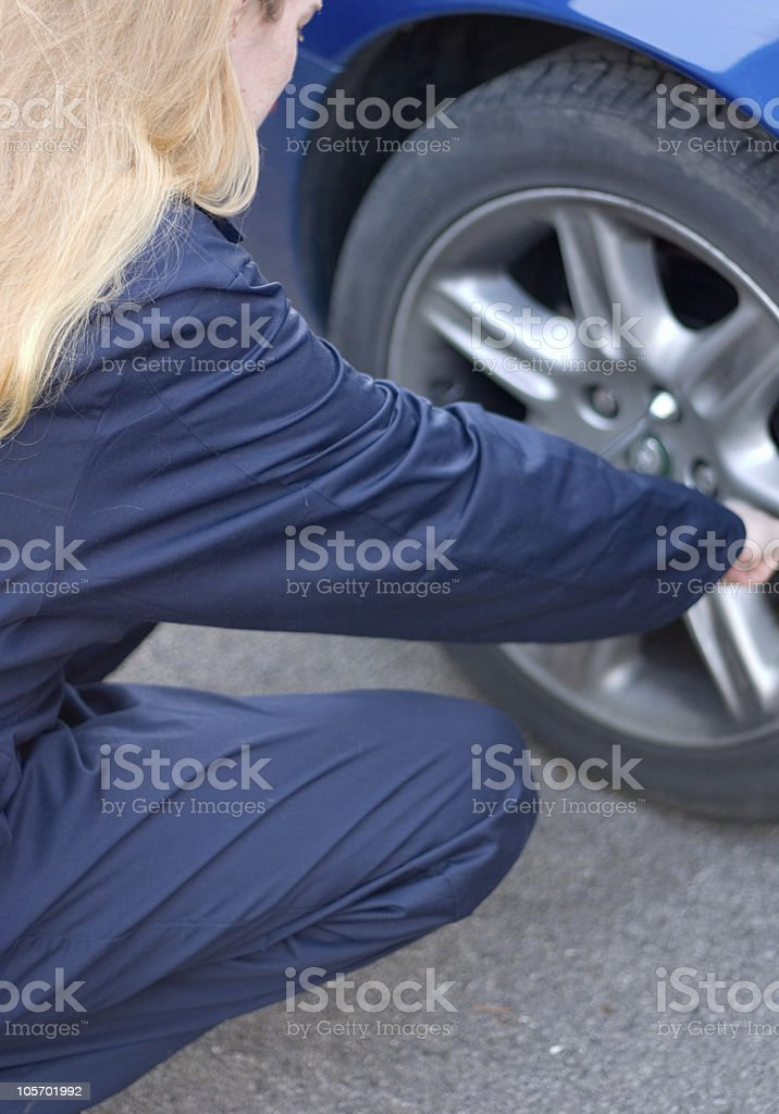 Girl Doing Up Wheel Nuts stock photo