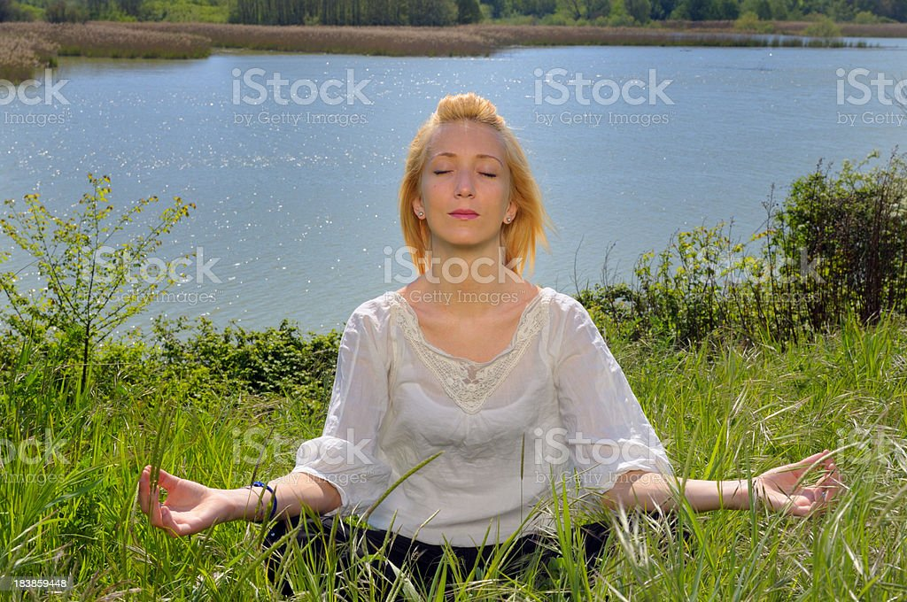 Girl Doing Yoga by the Lake royalty-free stock photo
