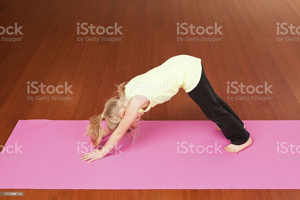 Girl Doing Yoga Downward Dog Pose in Studio royalty-free stock photo