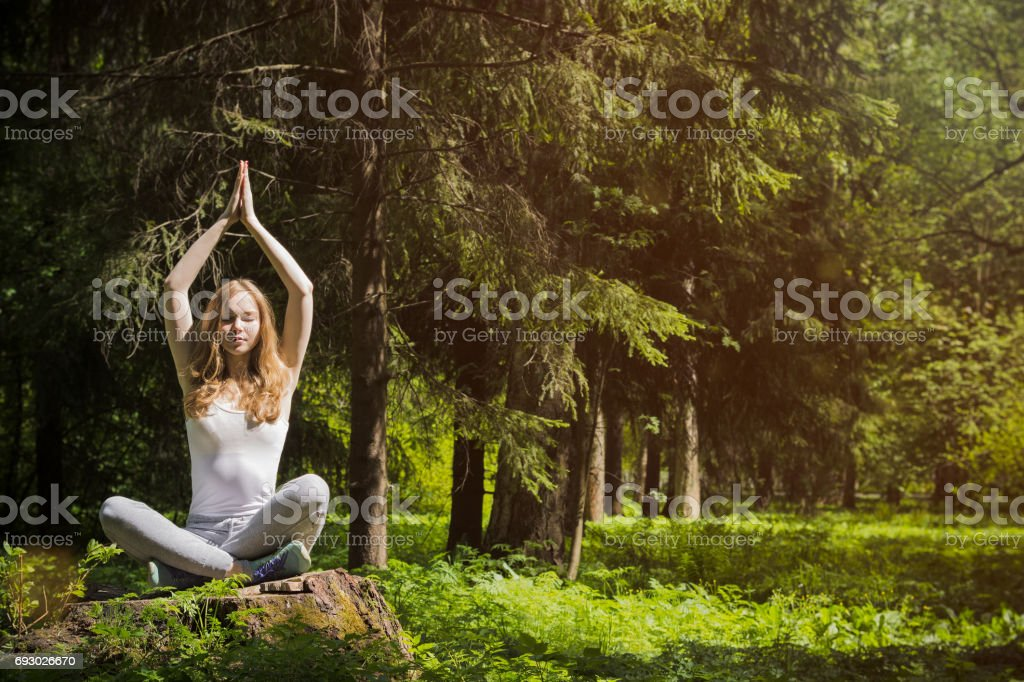 Girl doing yoga in nature. stock photo