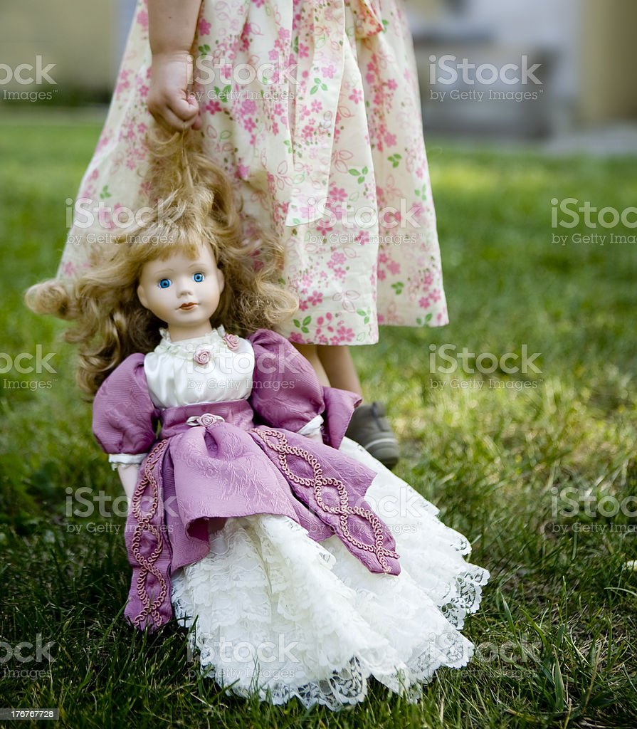 Girl dragging a vintage old porcelain doll royalty-free stock photo