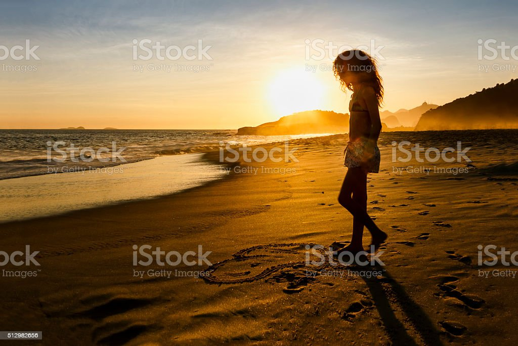 Girl Drawing a Heart on the Sand of Empty Beach stock photo