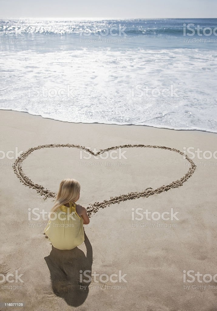 Girl drawing heart in sand on beach royalty-free stock photo