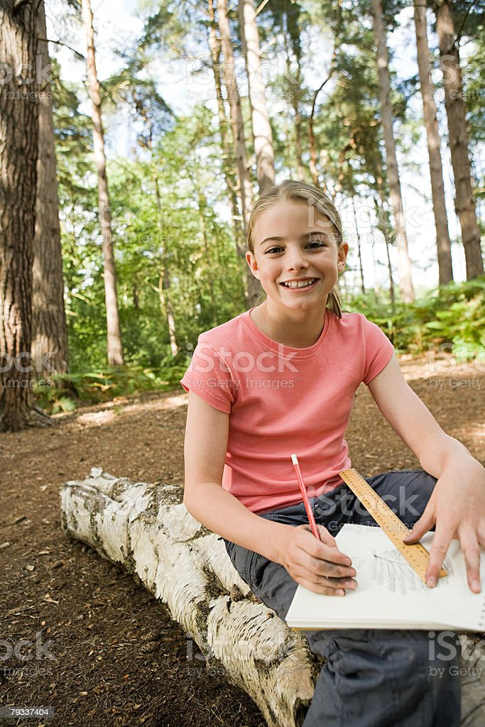 Girl drawing in forest stock photo