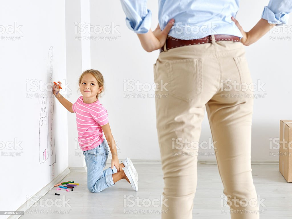 Girl drawing on wall with crayons, mother watching stock photo