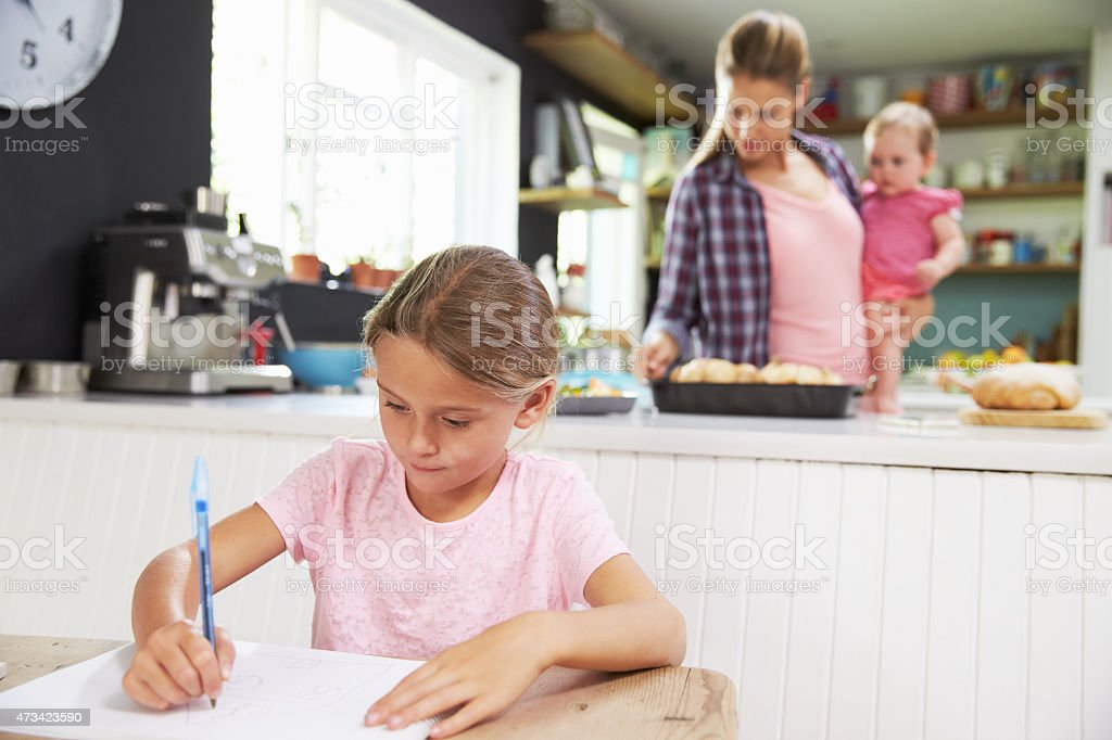 Girl Drawing Picture As Mother Prepares Meal In Kitchen stock photo