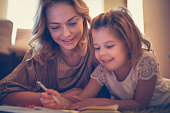 Girl drawing with her mother.