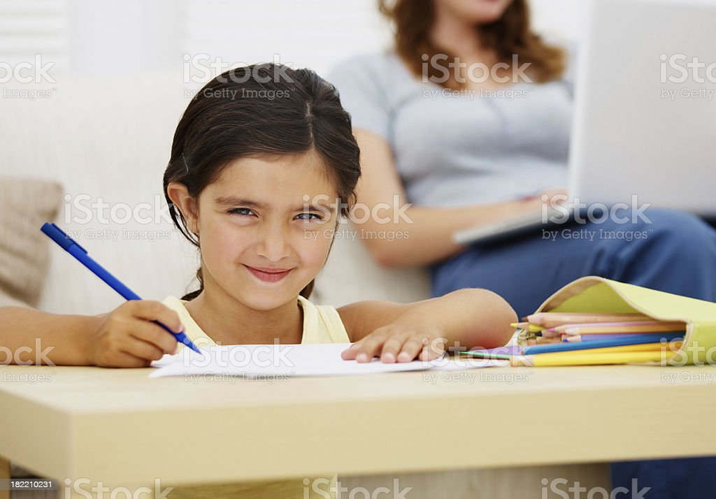 Girl drawing with mother in the background royalty-free stock photo