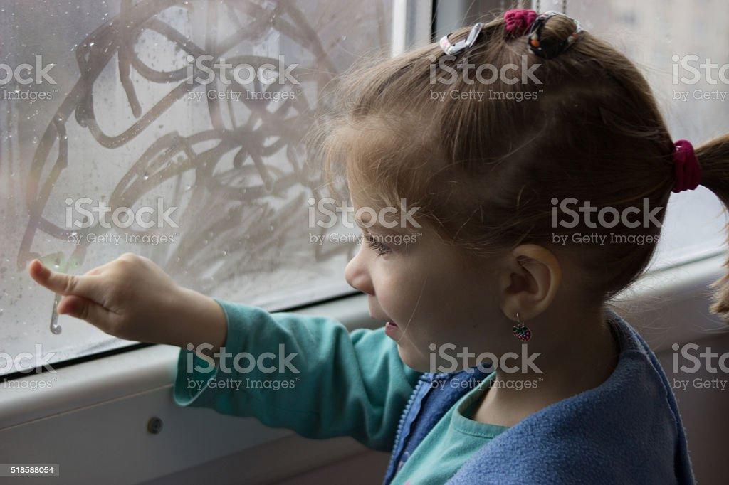 girl draws a finger on glass stock photo