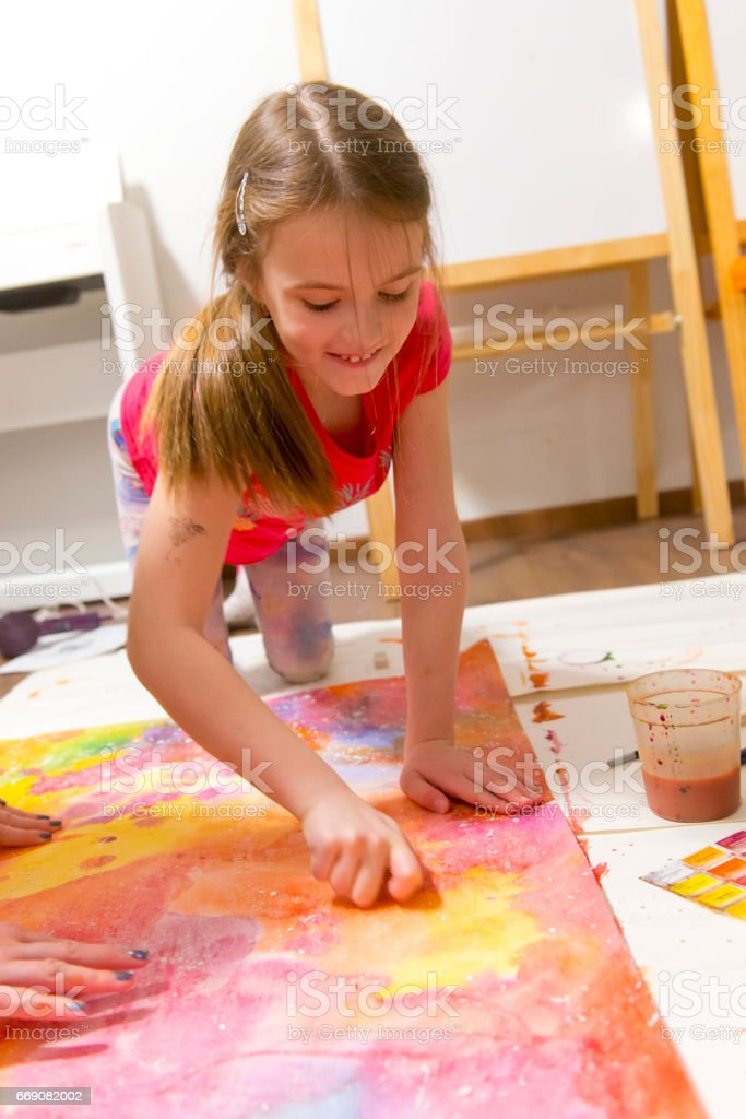 Girl draws home sitting on floor stock photo