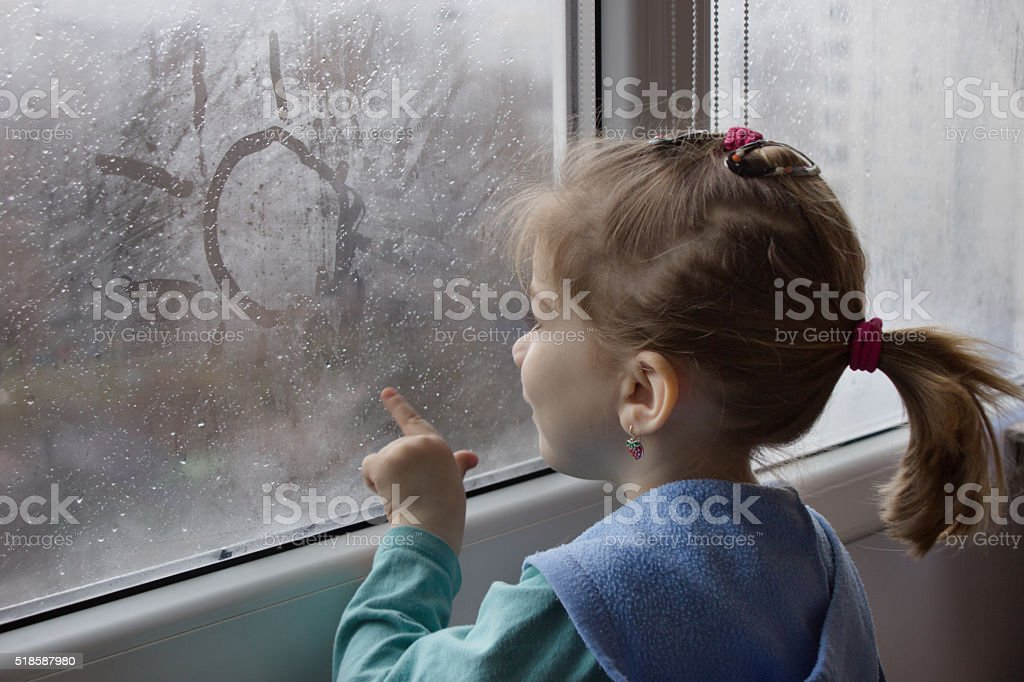 girl draws on glass stock photo
