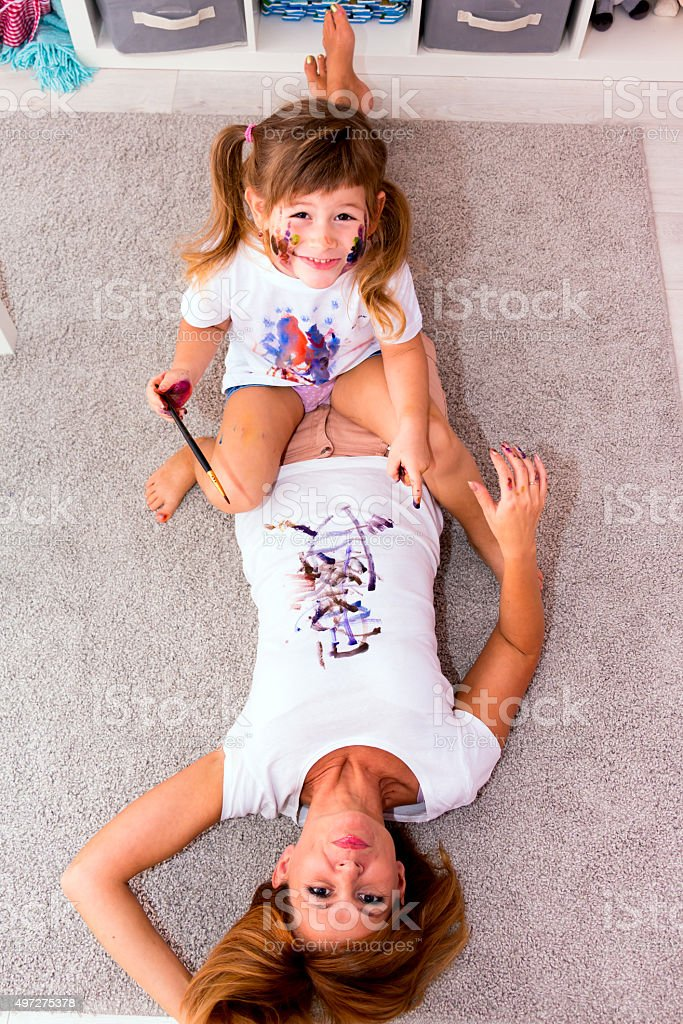 Girl draws paints on a T-shirt mother. stock photo