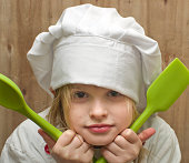 Girl dressed as chef with green silicone spoons