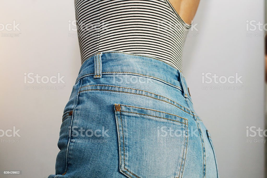 Girl dressed blue jeans and striped t-shirt back veiw . stock photo