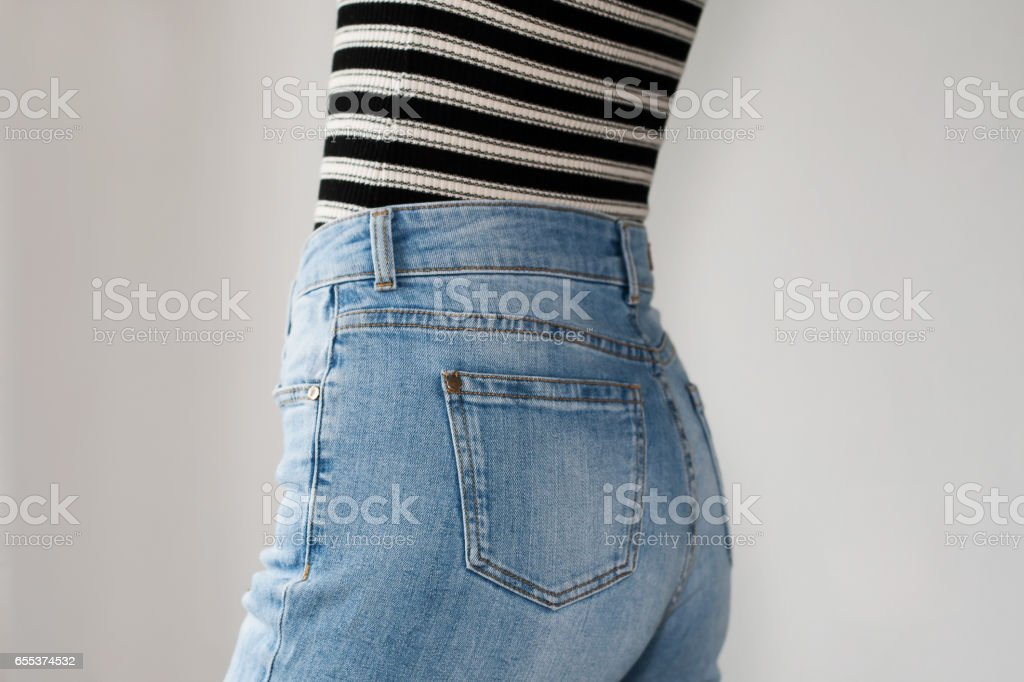 Girl dressed blue jeans and striped t-shirt, side view. Copy space. White background. stock photo