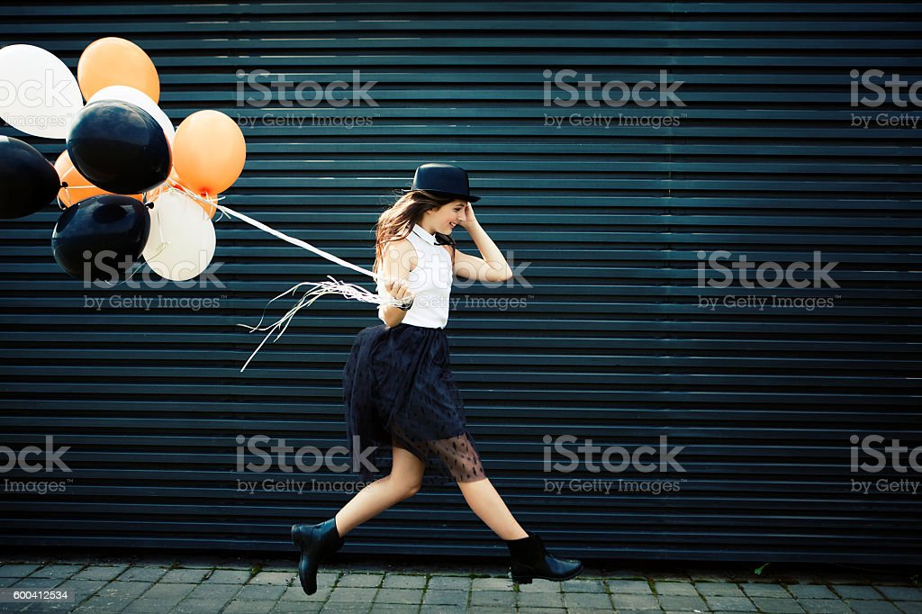Girl dressed for Halloween jumping with balloon stock photo
